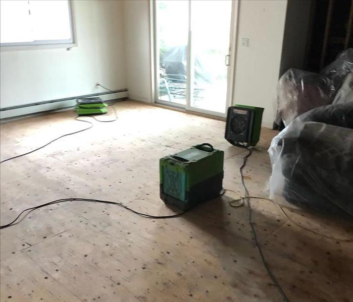 Room with an exposed subfloor and SERVPRO equipment