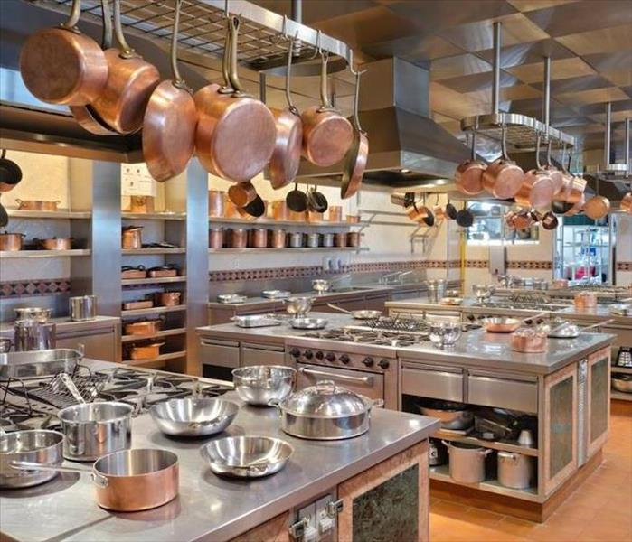 large commercial kitchen with copper pots hanging from hooks
