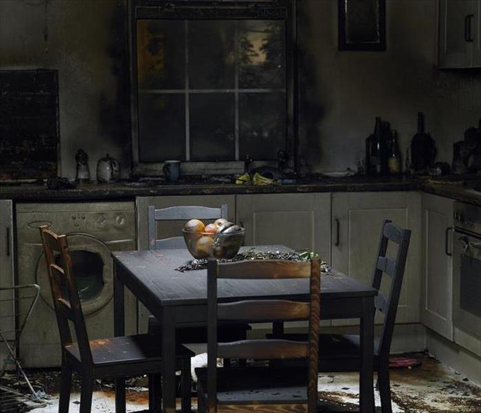 A table in a kitchen with fire damage and soot all over the kitchen.