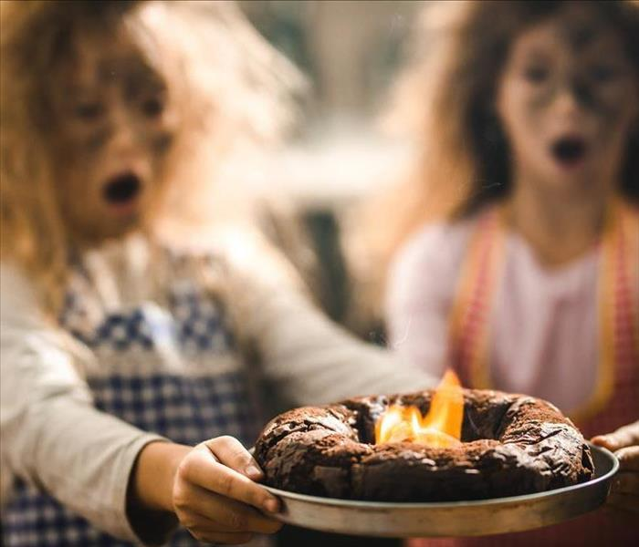 Two kids with ash on their faces, holding a burnt cake.